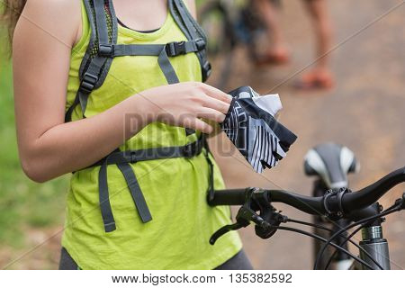 Mid section of young female biker wearing gloves