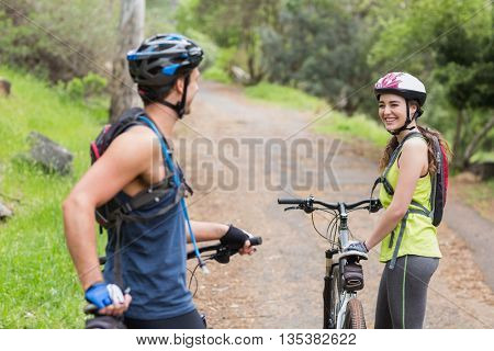 Happy couple with bikers looking at each other on footpath in forest