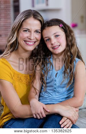 Happy mother and daughter smiling at camera in the house