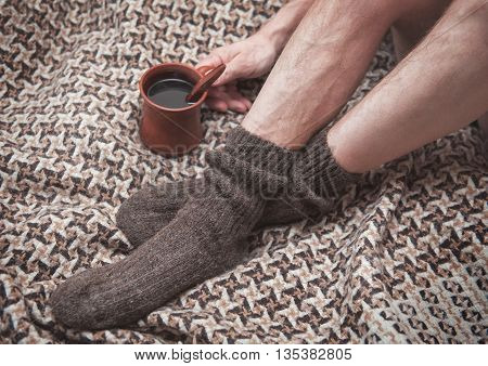 Man Feet On Woolen Plaid And Cup Of Coffee