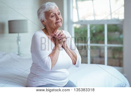 Senior woman joining hands while sitting on bed at home
