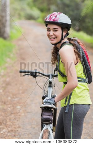 Portrait of cheerful woman with bike standing on footpath in forest
