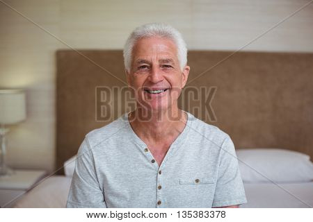 Portrait of smart senior man sitting on bed in room