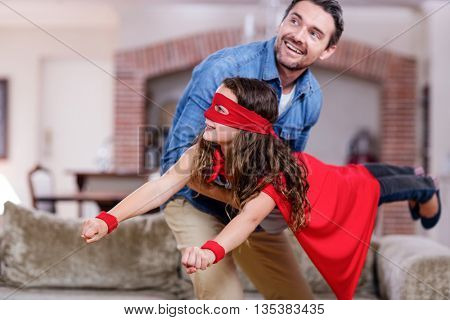 Father and daughter pretending to be superhero in living room at home