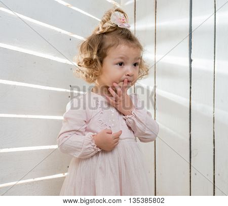 thoughtful little girl with funny hairstyle looking away in studio with wooden planked walls