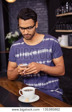 Man using his smartphone in a coffee shop