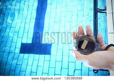 Close up of a hand holding a chronometer close to the swimming pool