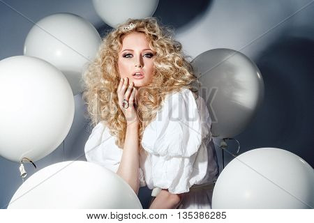 Seductive model in a white dress with balloons. Fashion-portret. Studio shot.