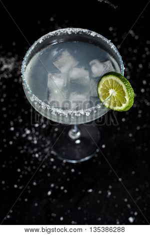 Classic mexican margarita cocktail on black background. Margarita glass full of ice, salt and lime on side. Black background with whites sea salt spots.