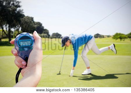 Composite image of a woman holding a chronometer to measure performance against female golfer picking up golf ball