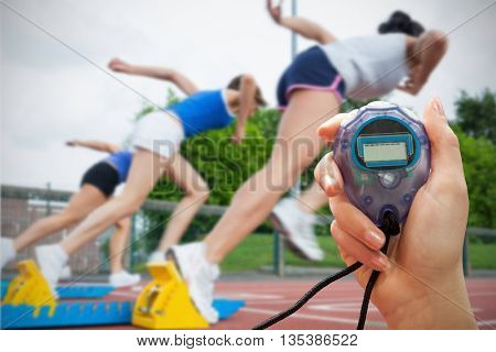 Composite image of woman is holding a stopwatch against women starting the race
