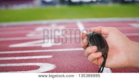 Close up of coach is holding a stopwatch against race track