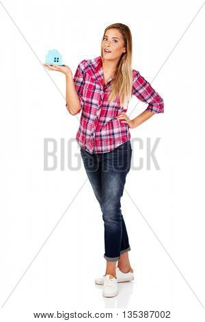 Smililing woman holding a paper house