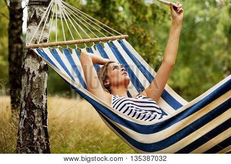 Young woman on hammock making a selfie