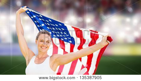 Portrait of happy sportswoman posing with an american flag against sports arena