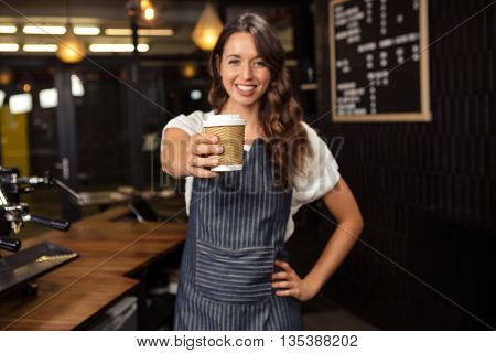 Smiling barista holding disposable cup at coffee shop