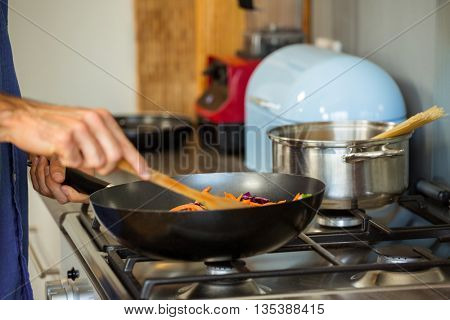 Mid section of man preparing food in the kitchen at home