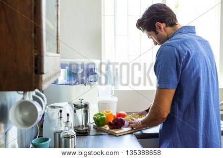 Man chopping vegetables at counter in kitchen