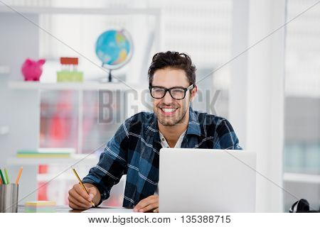 Portrait of young man working at his desk in the office
