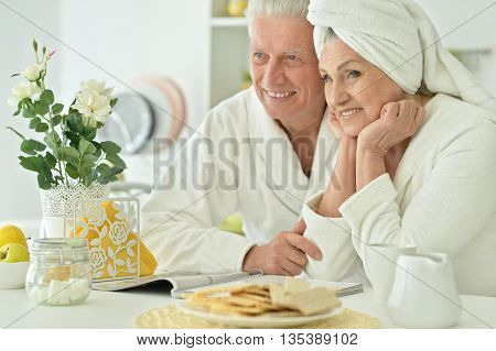 Portrait of mature couple in a bathrobe at kitchen