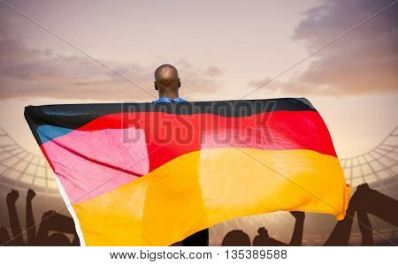 Rear view of sportsman is holding a German flag against football stadium with cheering crowd