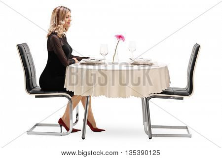 Studio shot of a young woman sitting alone at a restaurant table and waiting for her date isolated on white background