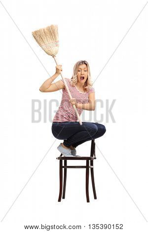 Vertical shot of a young scared woman swinging with a broom and chasing something isolated on white background