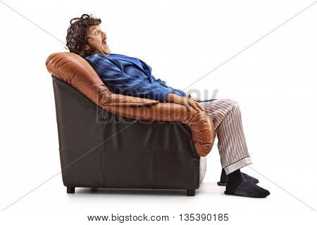 Profile shot of a scared young man seated in an armchair isolated on white background