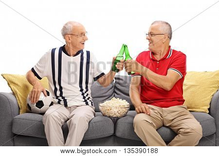 Two senior friends watching a game of football and drinking beer isolated on white background