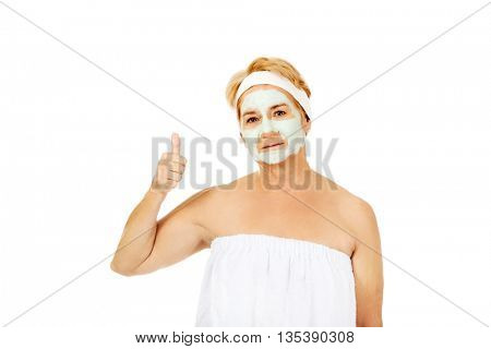 Smile elderly woman with facial mask shows thumb up