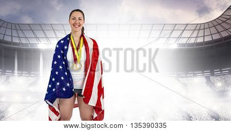 Athlete posing with american flag and gold medals around her neck in a stadium