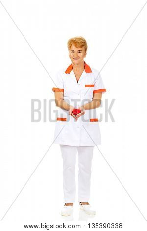 Smile elderly doctor or nurse holding red toy heart