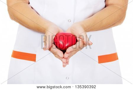 Elderly female doctor or nurse holding red toy heart