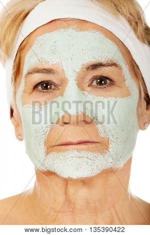Relaxed elderly woman in facial mask