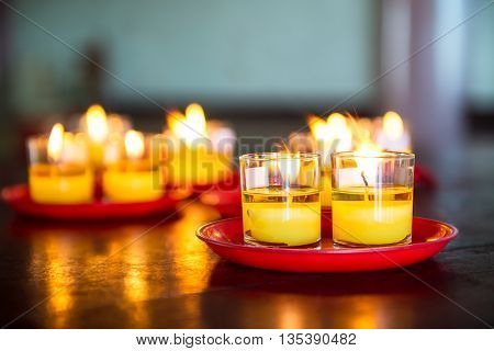 Yellow candle in glass catch fire and red plate on wooden table