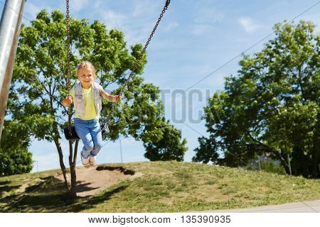 summer, childhood, leisure, friendship and people concept - happy little girl swinging on swing at children playground