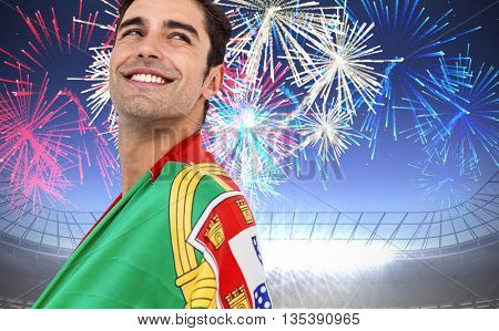 Athlete with portugal flag wrapped around his body against fireworks exploding over football stadium