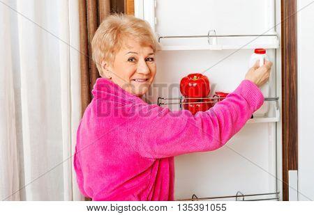 Senior woman taking a bottle of milk from fridge