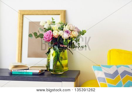 Vase with fresh roses in the room