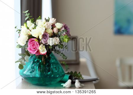 Beautiful bouquet of colourful roses in glass vase on white table