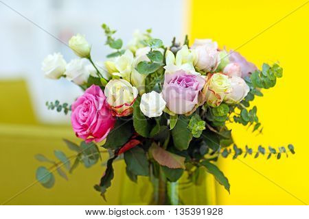Vase with fresh roses on wall background
