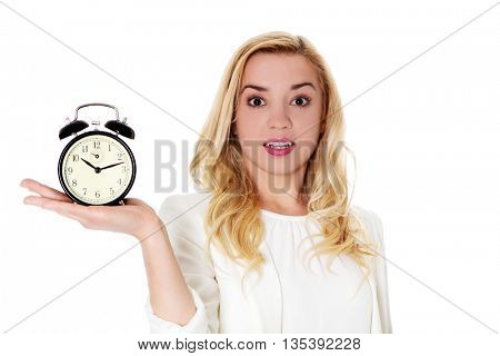 Blond woman showing alarm clock, isolated on white.