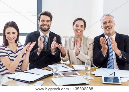 Workers are applauding and smiling at work