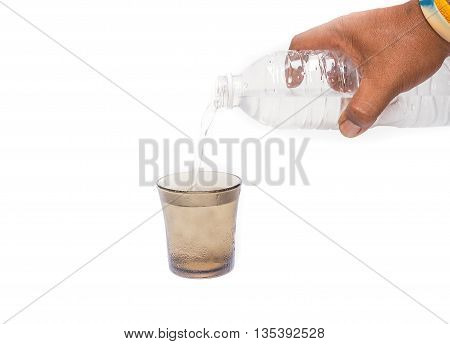 Male hand holding a bottle of Drinking water Pouring  ,into a Glass of very cold water, Drinking water thirsty.(select focus front Glass)