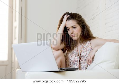 young attractive disappointed woman sitting at home living room couch using the internet for studying on laptop computer looking unhappy bored and in stress