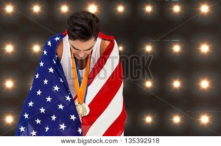 Athlete with gold medals and american flag looking down against spotlight background