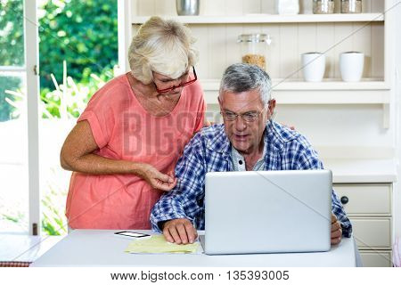 Wife discussing with senior man on laptop at table in kitchen