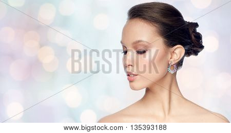 beauty, jewelry, accessories, people and luxury concept - close up of beautiful asian woman face with earring over blue holidays lights background