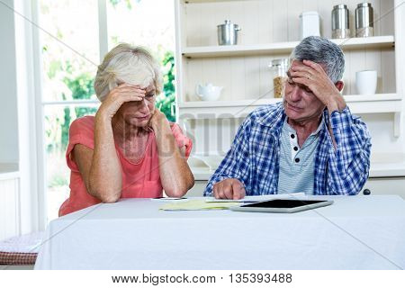 Worried senior couple with documents at table in kitchen