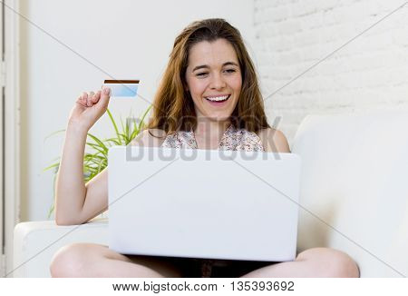 young attractive woman happy at home couch with laptop computer holding credit card doing internet on line shopping in e-commerce and electronic business concept